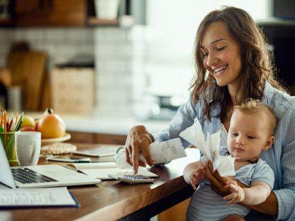 Mulher com bebé ao colo a organizar faturas para o IRS