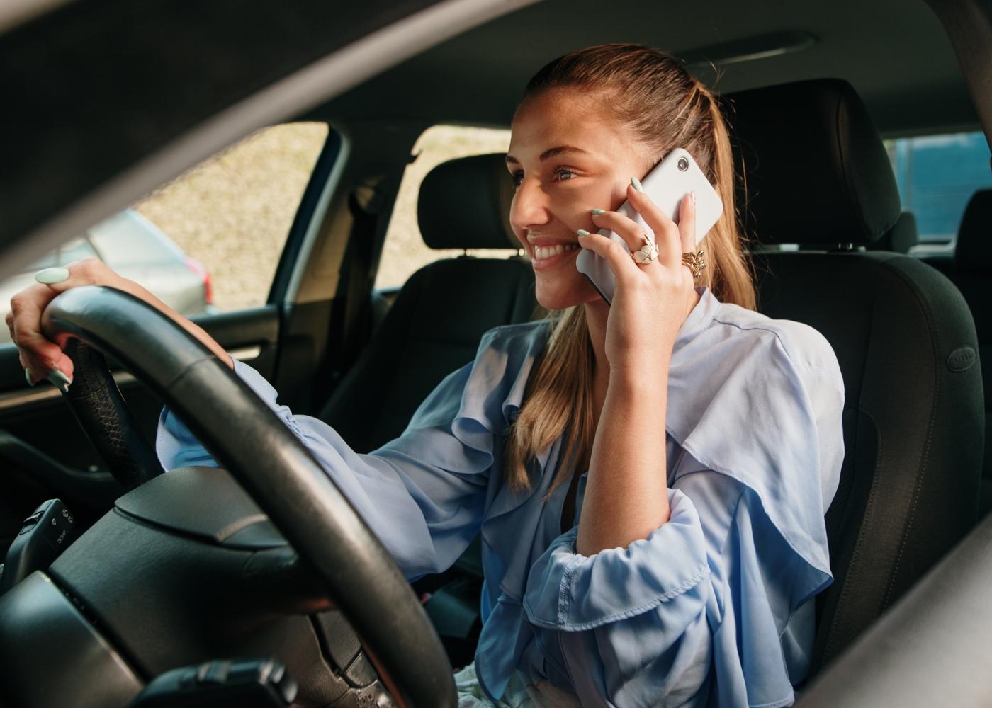 Mulher a conduzir e a falar ao telemóvel