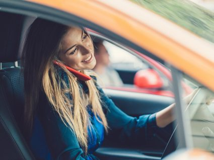Mulher a falar ao telemóvel enquanto conduz