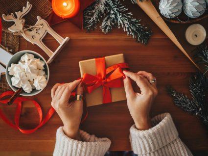 mulher a abrir uma caixa de presente natal