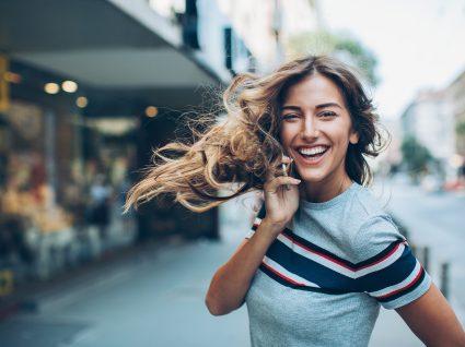 mulher a sorrir com um smartphone a nada rna rua