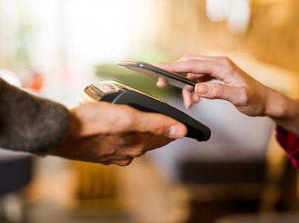 Mulher a fazer pagamento usando contactless com smpartphone