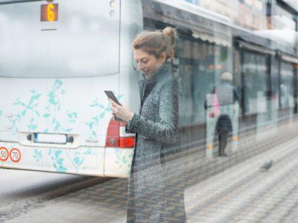 Mulher a ver horário de autocarro numa app de mobilidade
