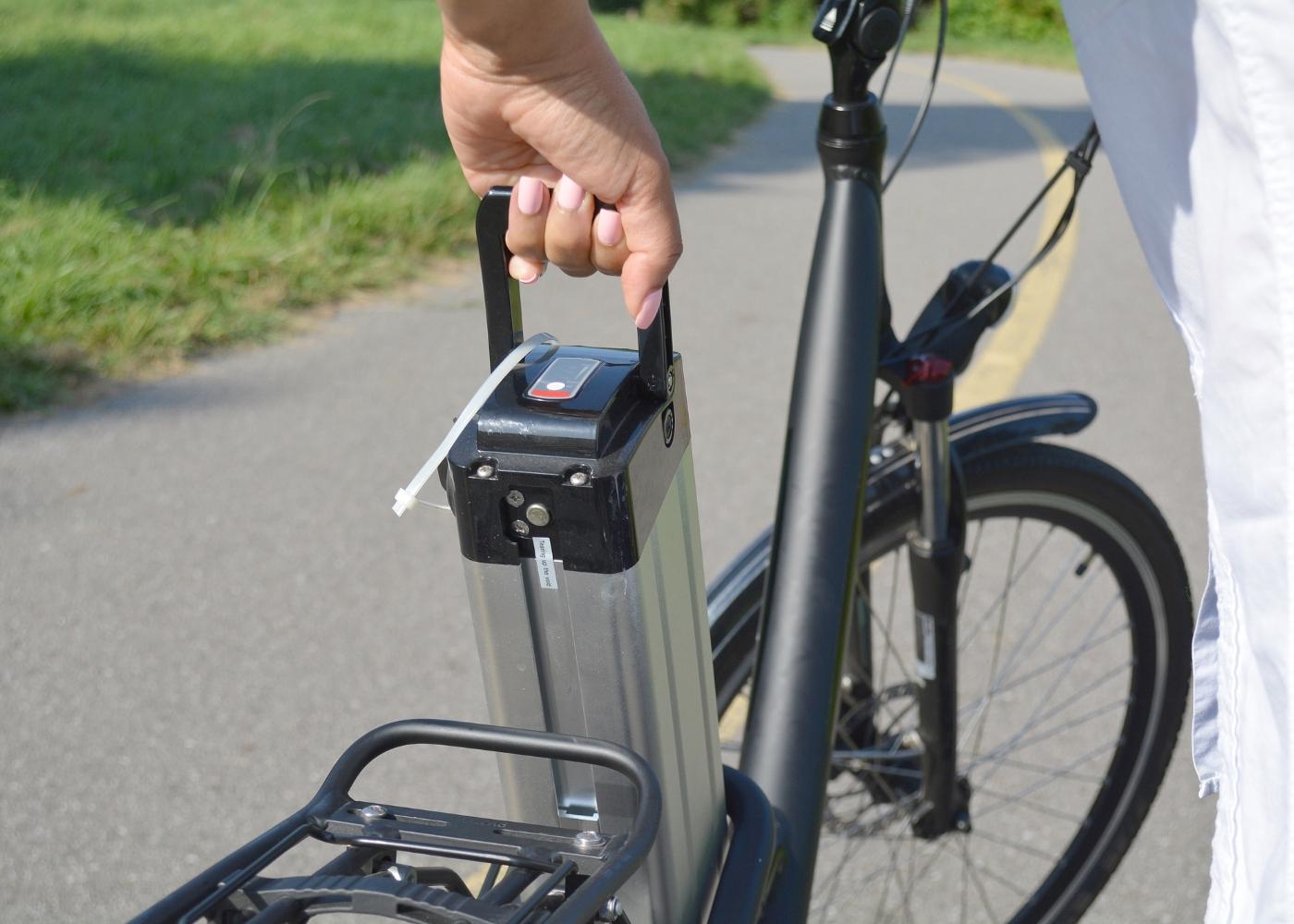 pessoa a retirar bateria das bicicletas elétricas