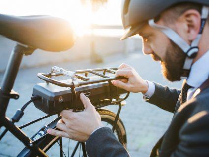 ciclista a colocar bateria na sua bicicleta elétrica
