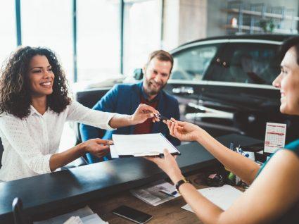casal a analisar com funcionária de stand as melhores opções para comprar carro