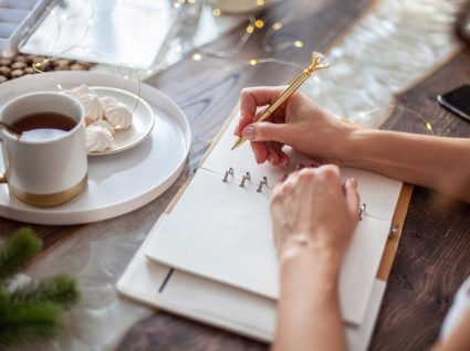 mulher a escrever num caderno as suas resoluções financeiras para o novo ano
