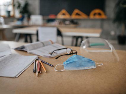 mesa de escola com máscara, viseira e materiais escolares