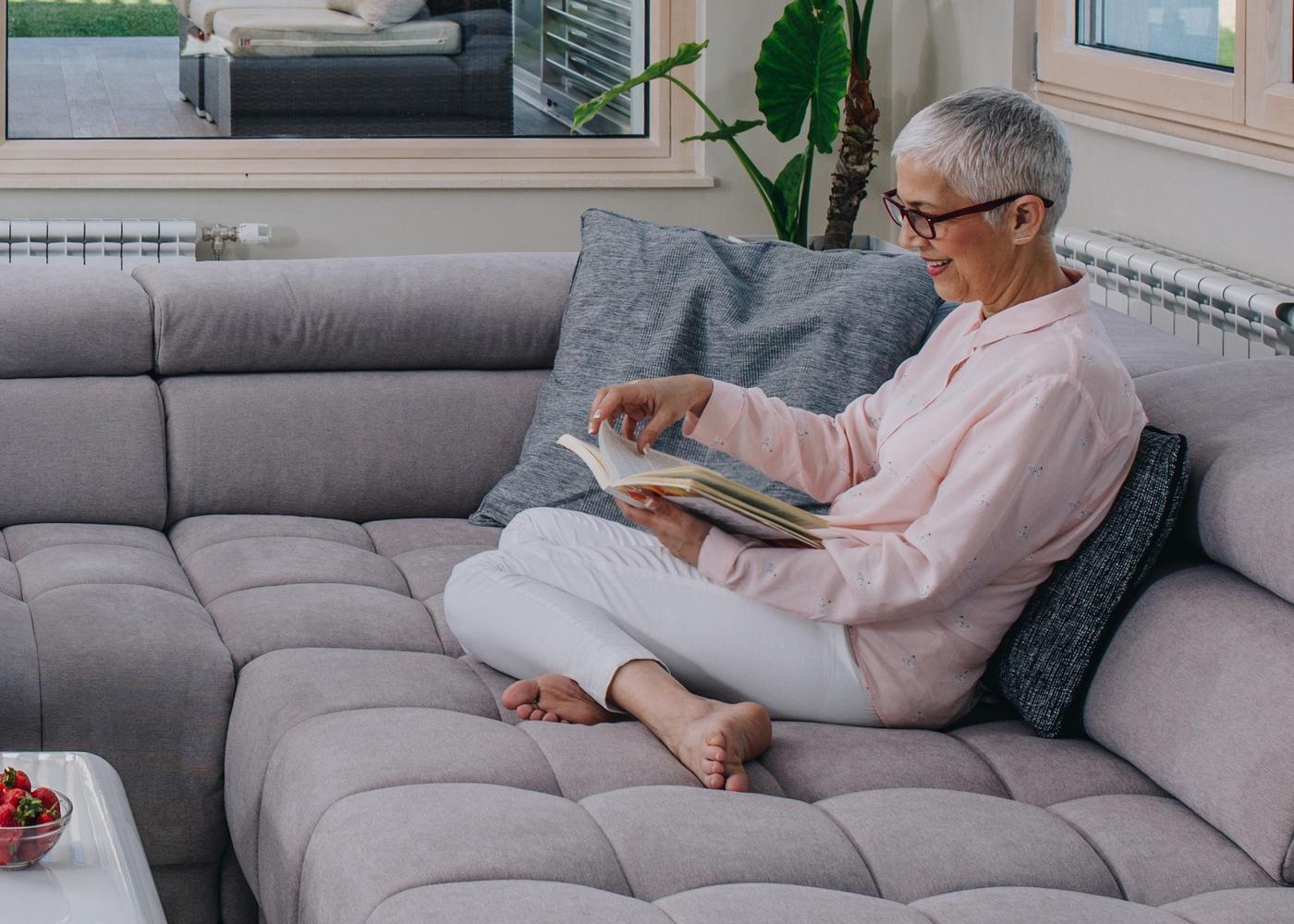 Idosa a ler um livro sentada no sofá