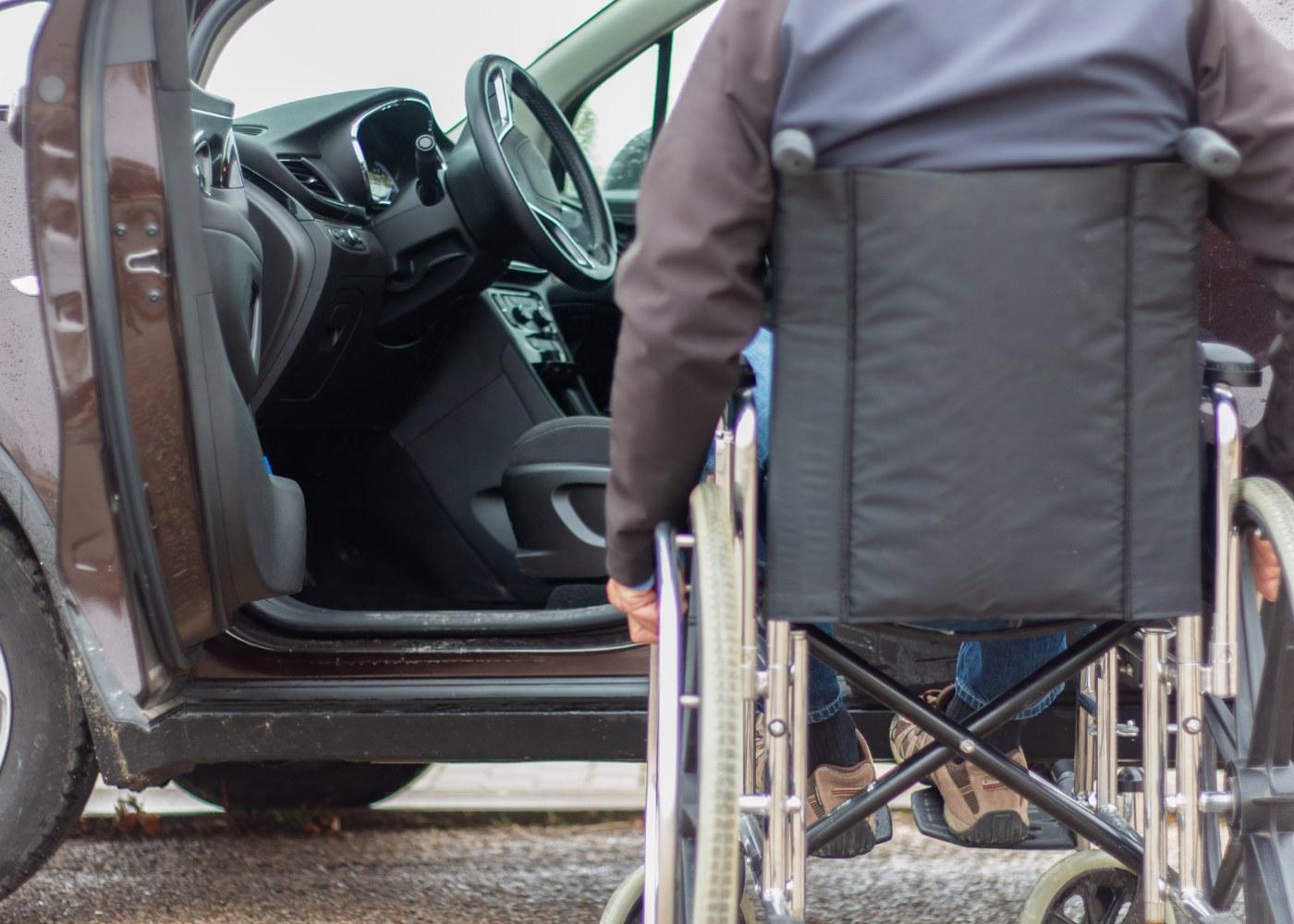 condutor de cadeira de rodas a entrar para carro adaptado
