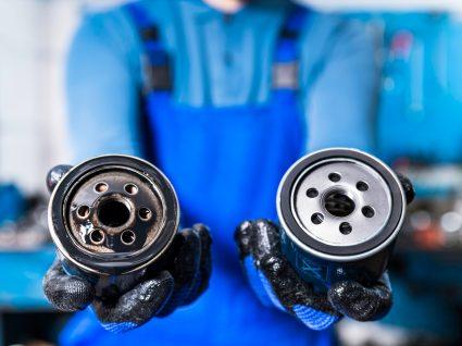 mecânico a mostrar filtro do óleo do carro usado e novo
