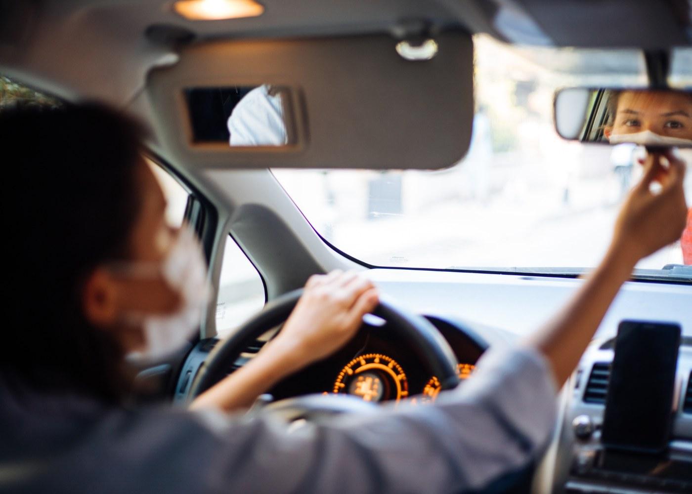 mulher com máscara a ajustar o espelho retrovisor do carro