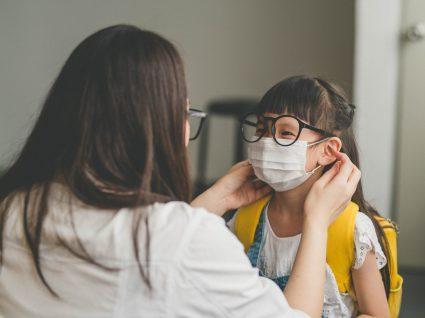 mulher a colocar máscara a criança