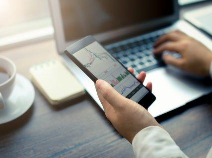 Mulher a investir em ETFs via smartphone