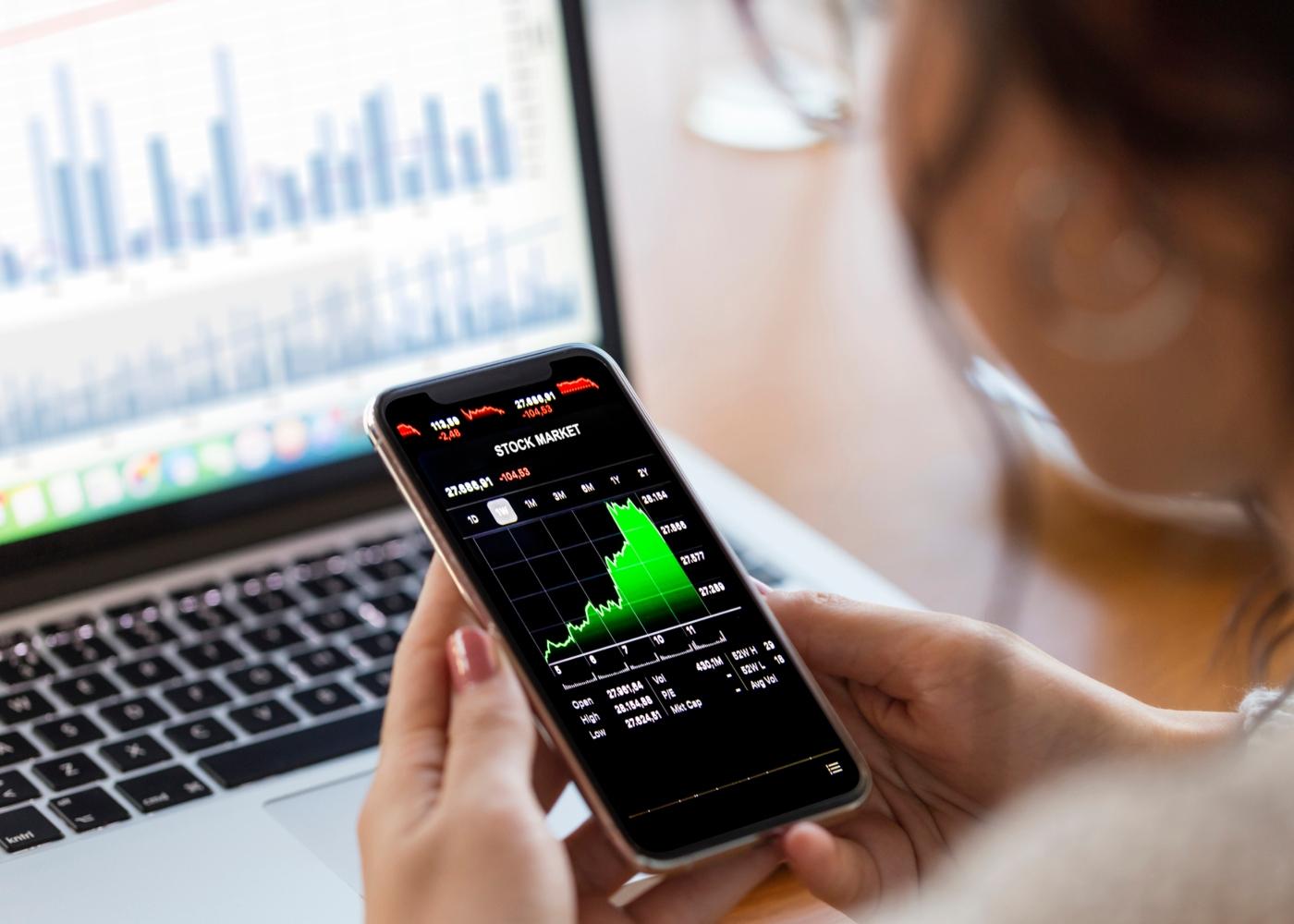 Mulher a investir na Bolsa via smartphone
