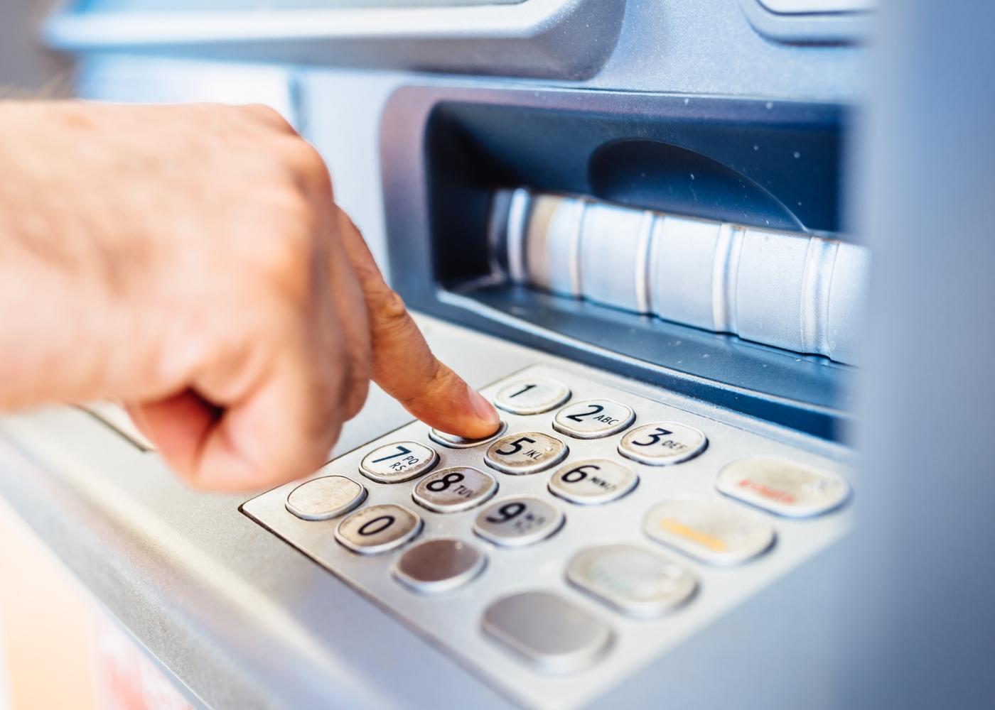 Homem a levantar dinheiro numa caixa Multibanco