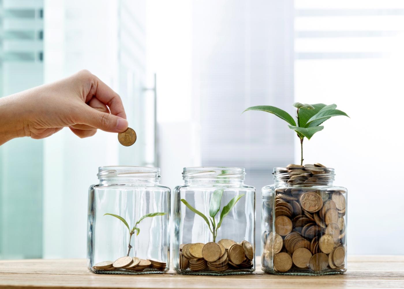 Frascos com moedas a ilustrar o crescimento de poupanças