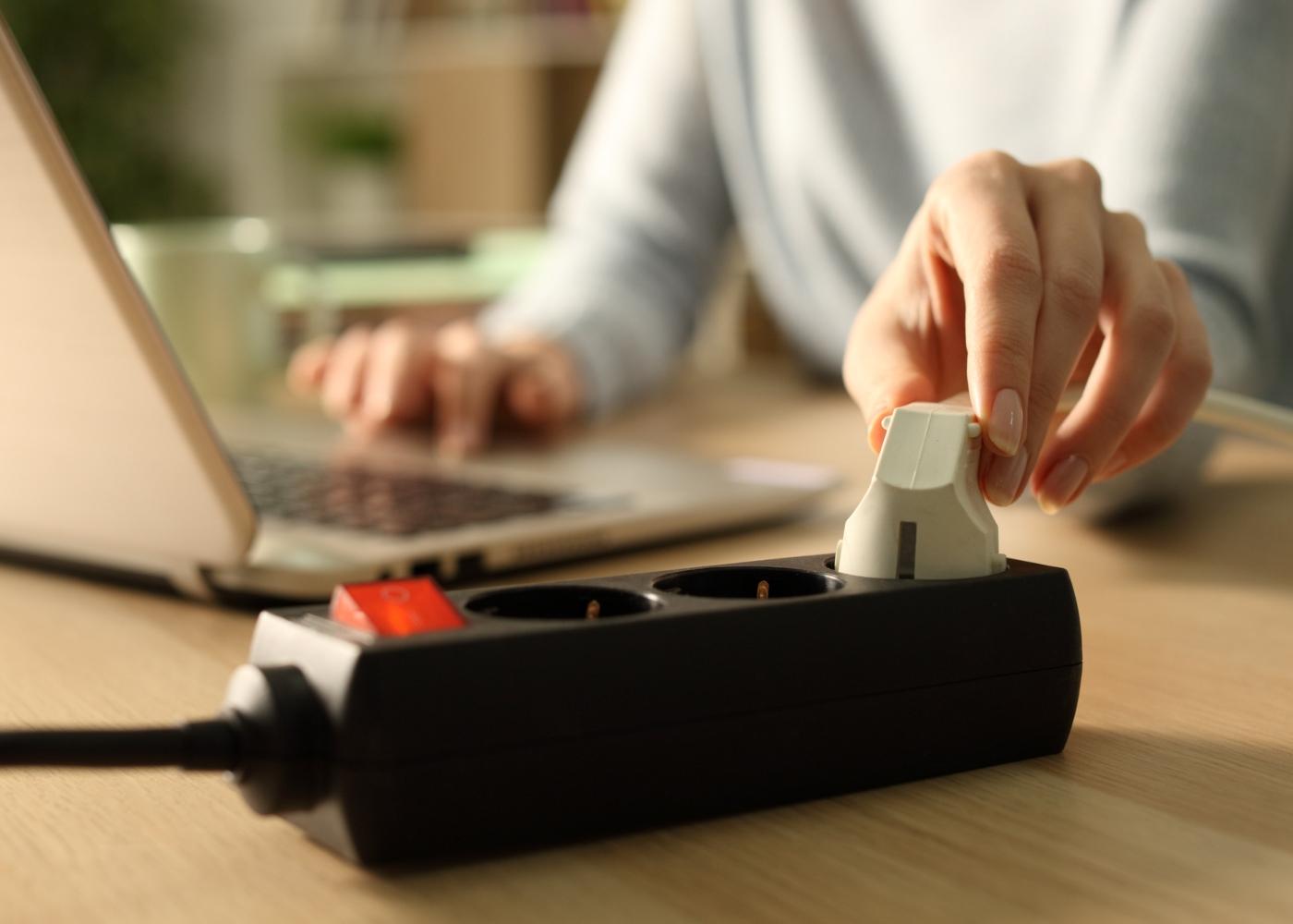 Mulher a ligar bateria de computador a tomada elétrica