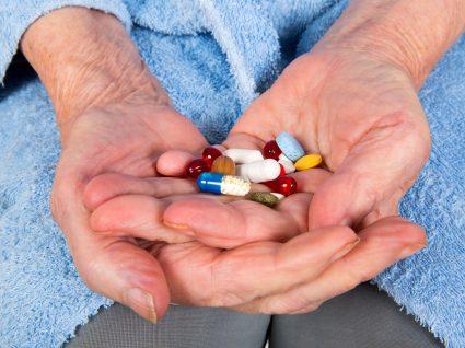 mãos de uma mulher idosa a segurar vários medicamentos
