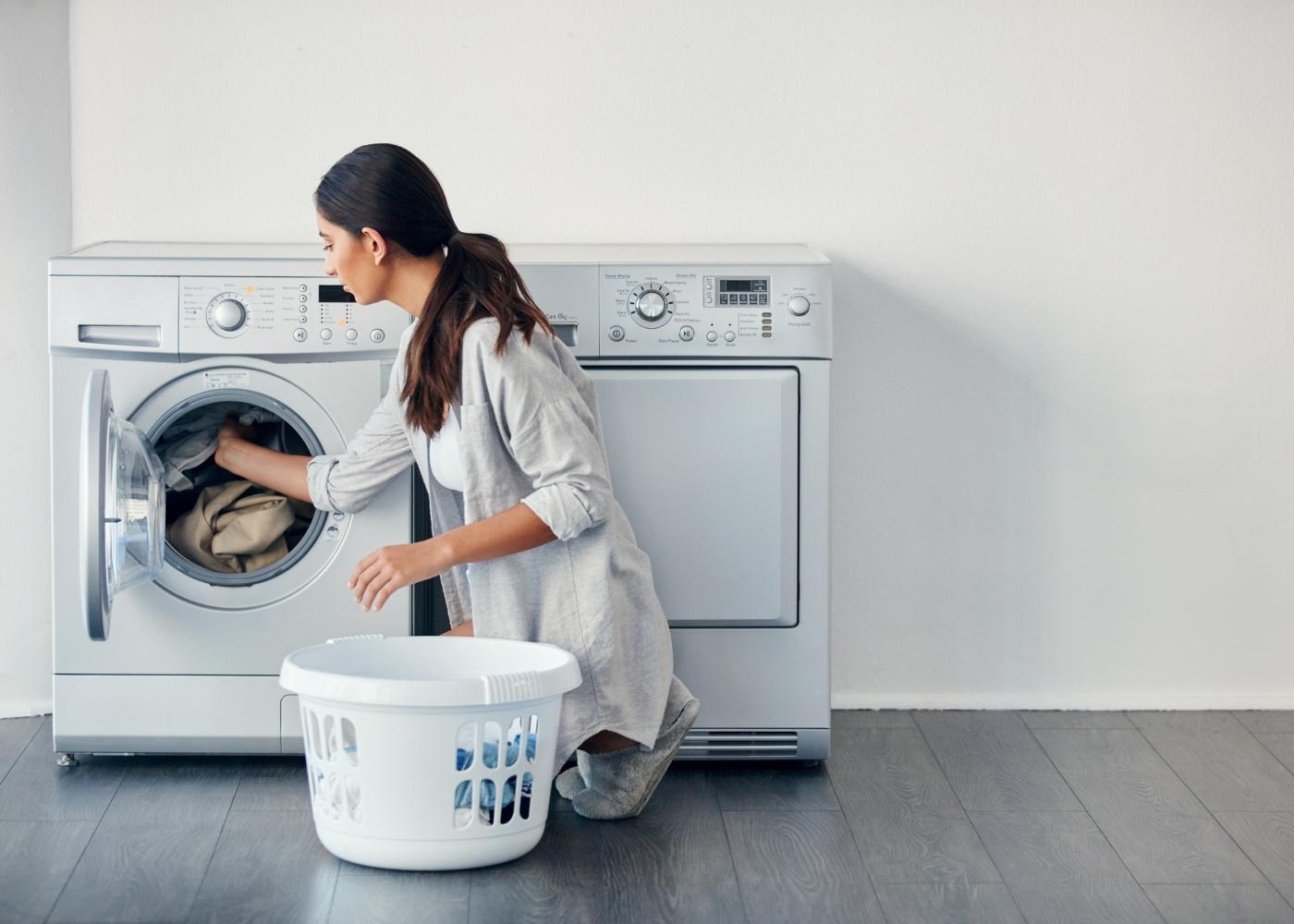 mulher a colocar a roupa na máquina para lavar