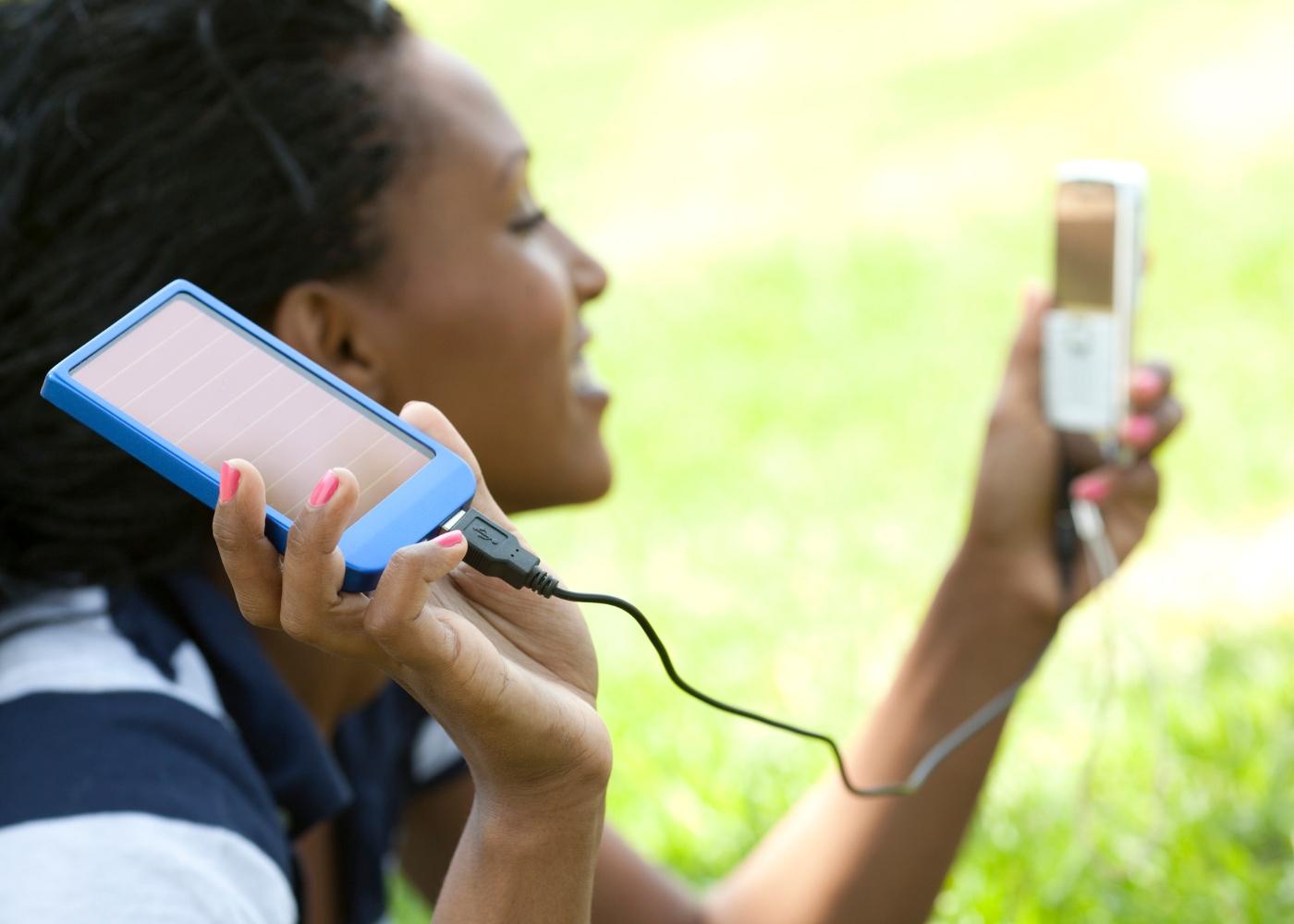 jovem a carregar telemóvel a energia solar