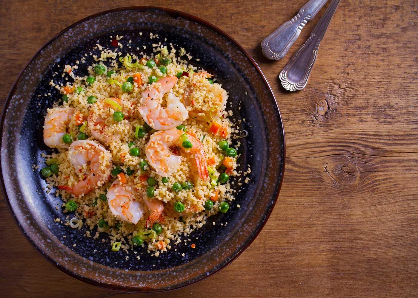 Cuscuz de legumes com camarão em prato escuro