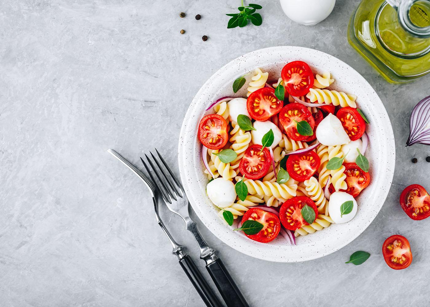 Salada de massa, tomate e mozzarella fresco no prato em fundo cinza