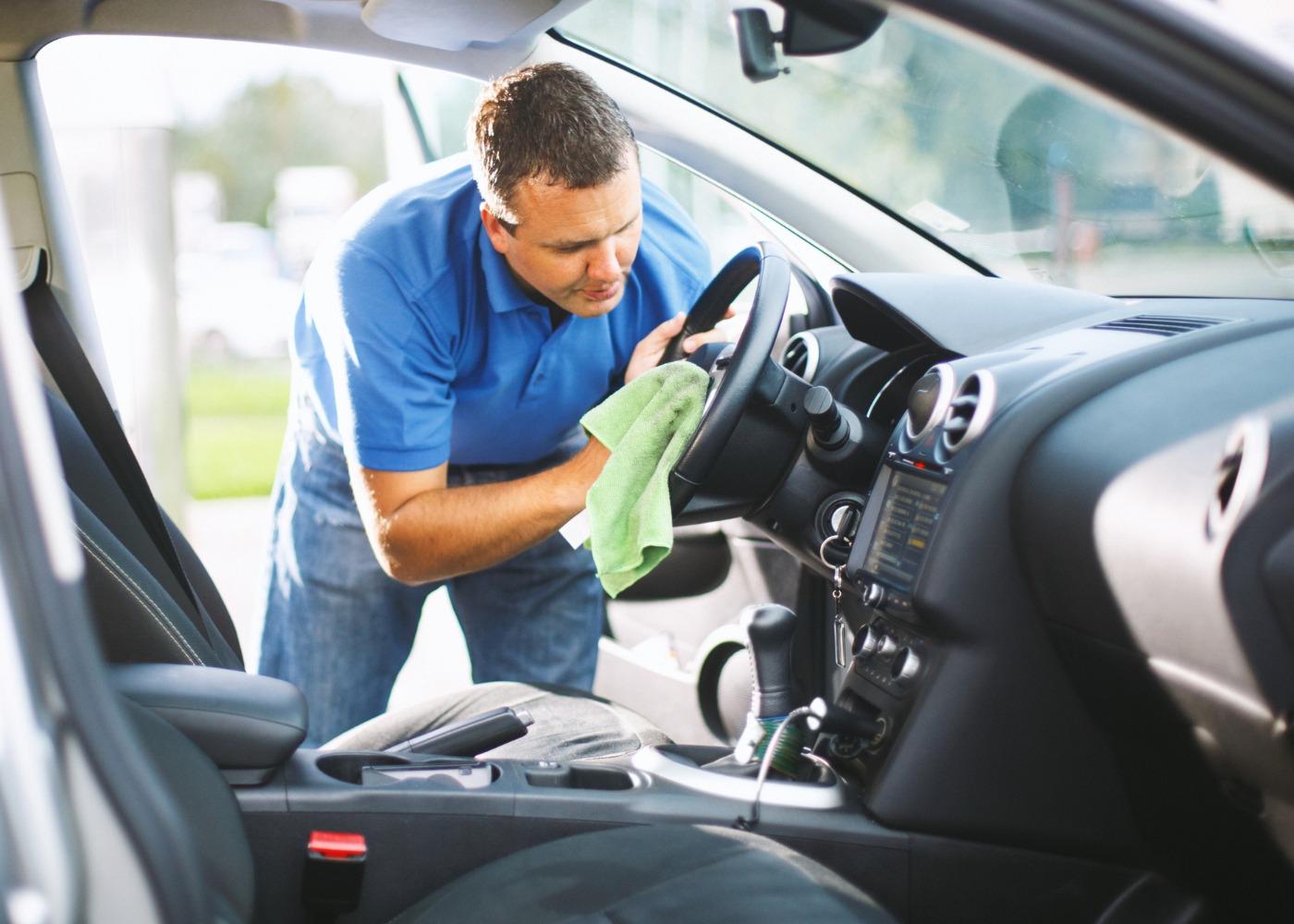 Homem a limpar o interior do carro